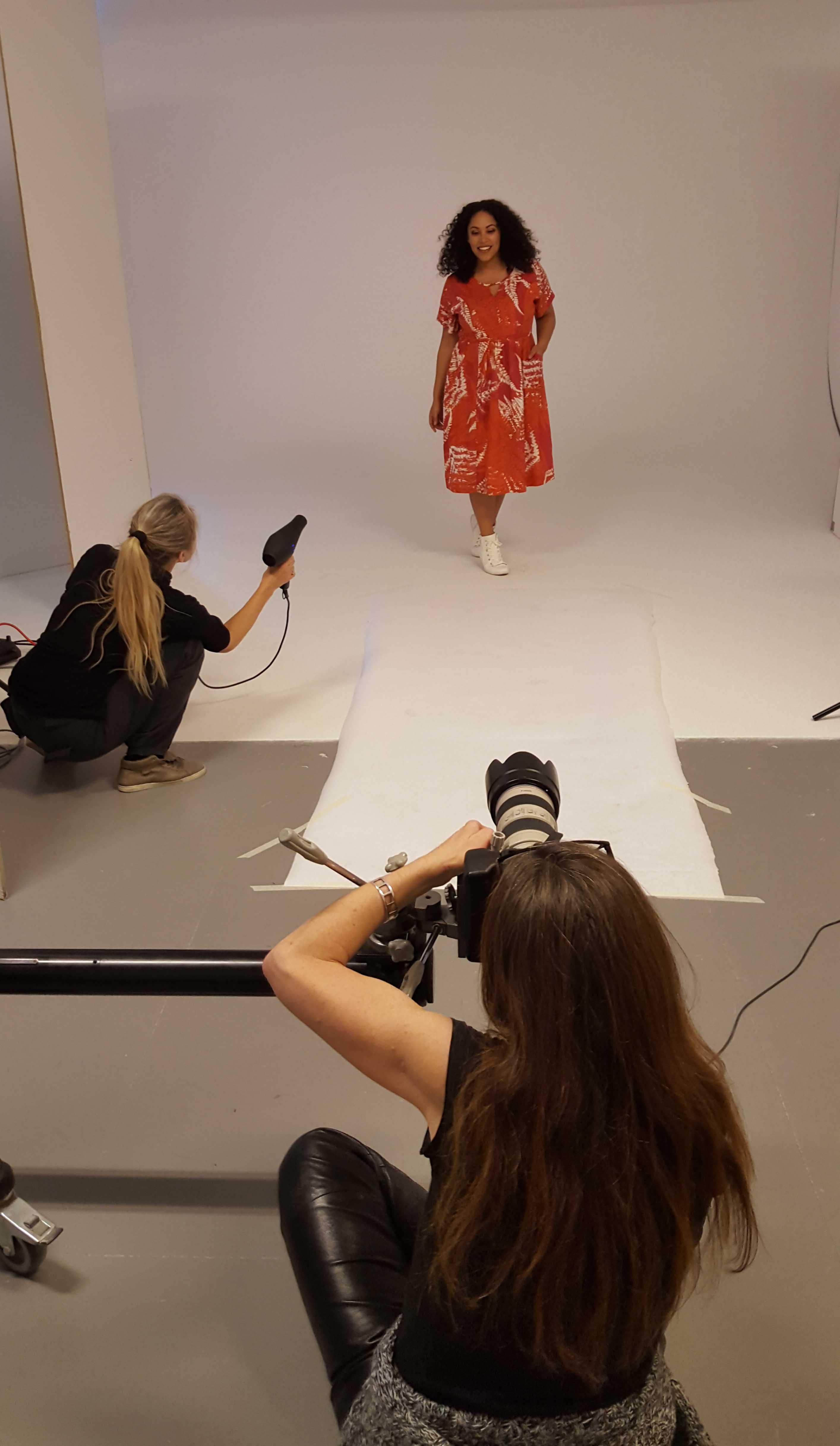 En tjuvtitt på nya färgstarka klänningen Noor.  Audrey som aldrig fått göra ett modejobb i sneakers är bekväm och glad. Mia ger luft i lockarna och Camilla fotograferar.